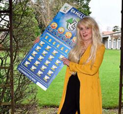 Melissa Ede holding huge Blue National lottery scratchcard